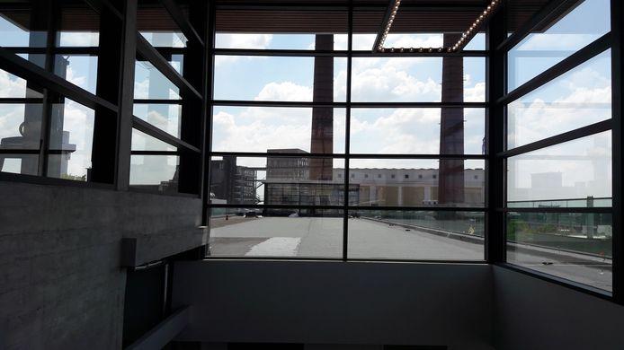 Op het platte dak van TQ4 staat een kubus met veel glas die door alle bedrijven op Strijp-T in Eindhoven gebruikt kan worden als een ruimte om bijeenkomsten te organiseren. Hier is ook toegang tot de daktuin.