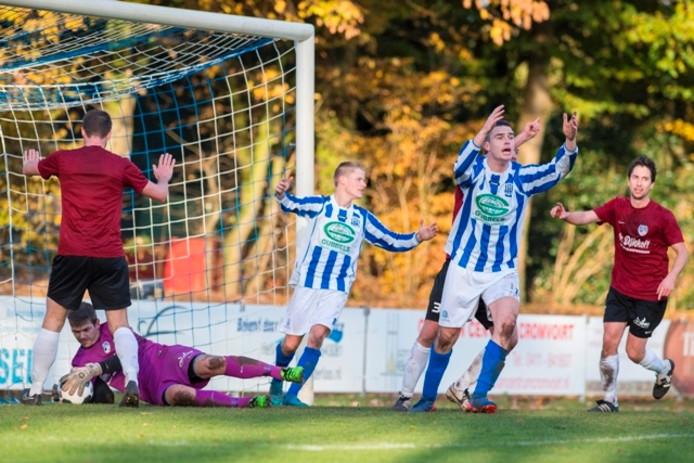 Heeswijk-keeper Patrick Lunenburg (op de grond) voorkomt ternauwernood een goal van Helvoirt.