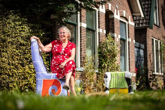 Guusje Beverdam, zittend op de stoel voor haar huis die zo kenmerkend is voor haar werk.