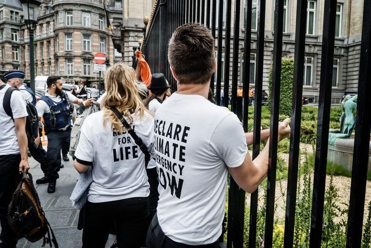 Activisten lijmen zich vast aan het hek rond het federaal parlement. Beeld Eric de Mildt
