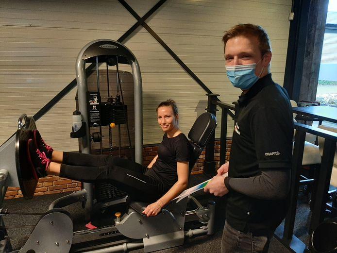 Fysiotherapeut Rutger Pollemans van ZorgSaam begeleidt ex-coronapatiënte Marjolein Leemhuis, die in sportschool DRW werkt aan het herstel van haar conditie.