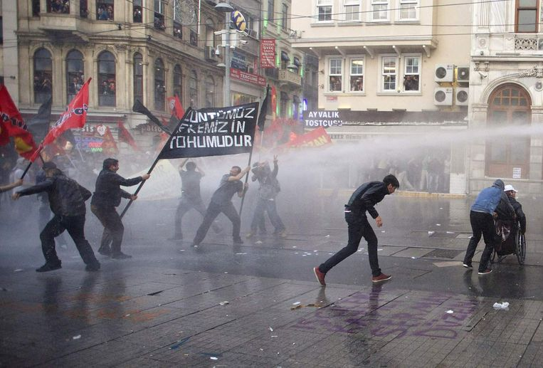 Betogers in Istanboel zoeken dekking voor de waterkanonnen van de politie. Beeld REUTERS