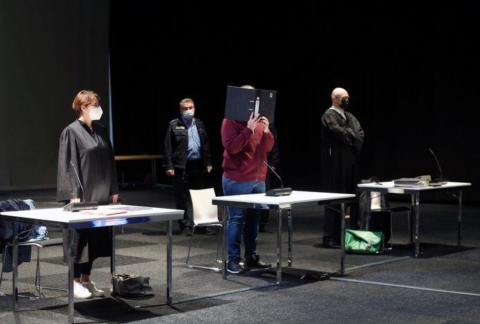 Maurice Pahler (m) verstopt zijn gezicht achter een ordner tijdens de fotosessie bij het begin van de rechtszaak tegen hem voor de rechtbank in Kassel.