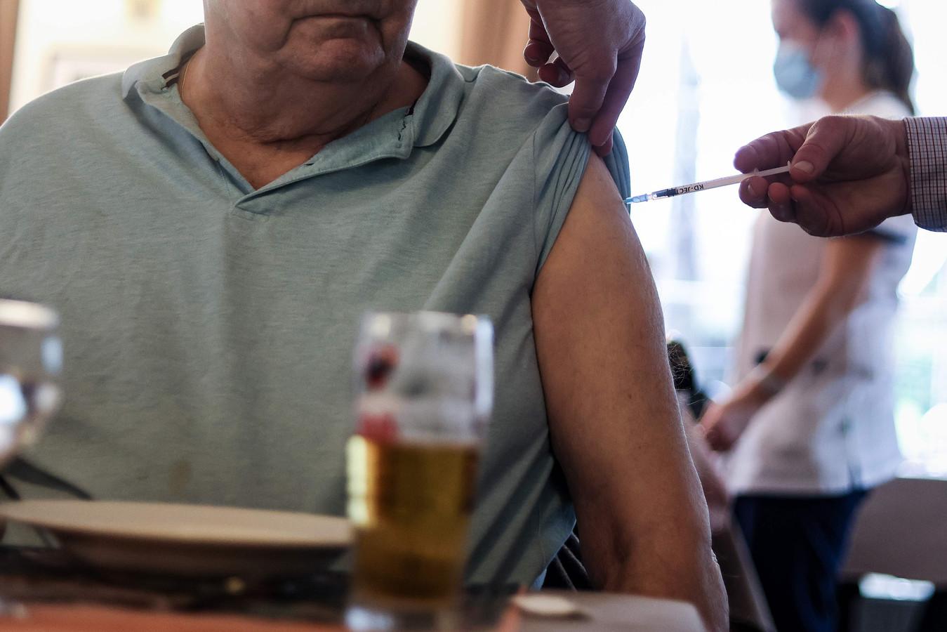 Un résident d'une maison de repos se fait vacciner à Bruxelles.