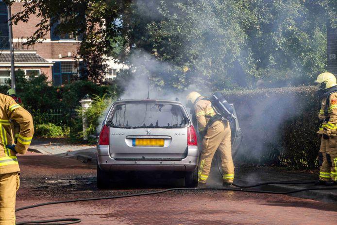 De auto wordt geblust door de aanwezige brandweerlieden.