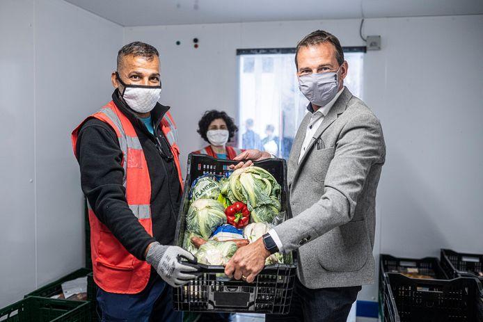 Minister Wouter Beke (CD&V) helpt Rachid Ghassan Fadhel van Foodsavers even een handje in de koelcel.