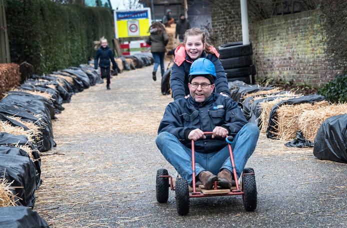 Chauffeur mét passagier tijdens de zeepkistenrace van carnavalsvereniging De Wielwaoiers uit Nederasselt.