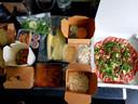 Carpaccio, gamba's met noodles, paksoi en sojabonen, de hele bestelling en de salade van gerookte zalm en crostini's.