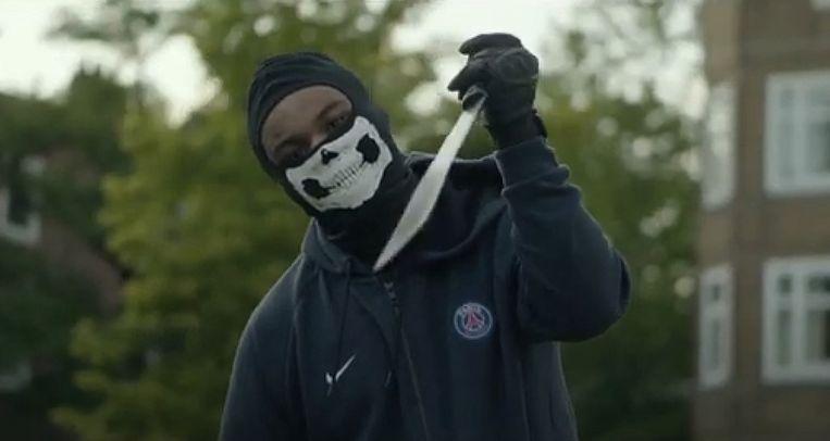 Karakteristiek beeld uit een Nederlandse drillrapvideo: bedekte gezichten, grote messen.  Beeld YouTube