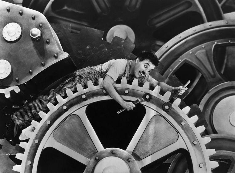 Charlie Chaplin als noeste arbeider in 'Modern Times' uit 1936. Beeld Bettmann Archive