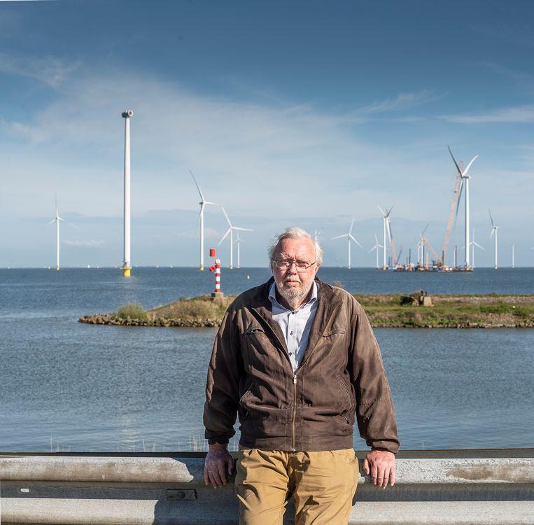 Albert Koers met op de achtergrond een het in aanbouw zijnde windmolenpark bij de Afsluitdijk.  Beeld Harry Cock / de Volkskrant