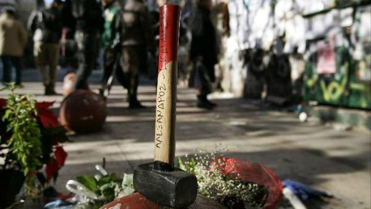 Een hamer met de Griekse tekst: 'Alexdros-Wraak' siert een herdenkingsplaats voor de vermoorde 15-jarige Alexandros Grigoropoulos (AP) Beeld