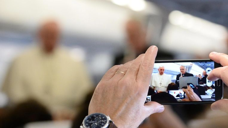 Iemand maakt een foto van Paus Franciscus in het vliegtuig. Beeld epa
