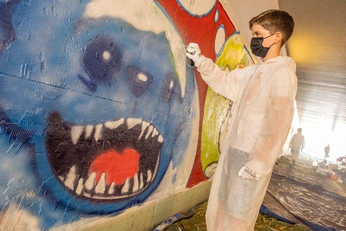 Lazlo Zwanenburg (12) versiert de fietstunnel van de Statenlaan onder de Schroeweg in Middelburg met nieuwe graffiti. De gemeente Middelburg laat in meerdere tunneltjes in de stad kunst maken door jongeren.