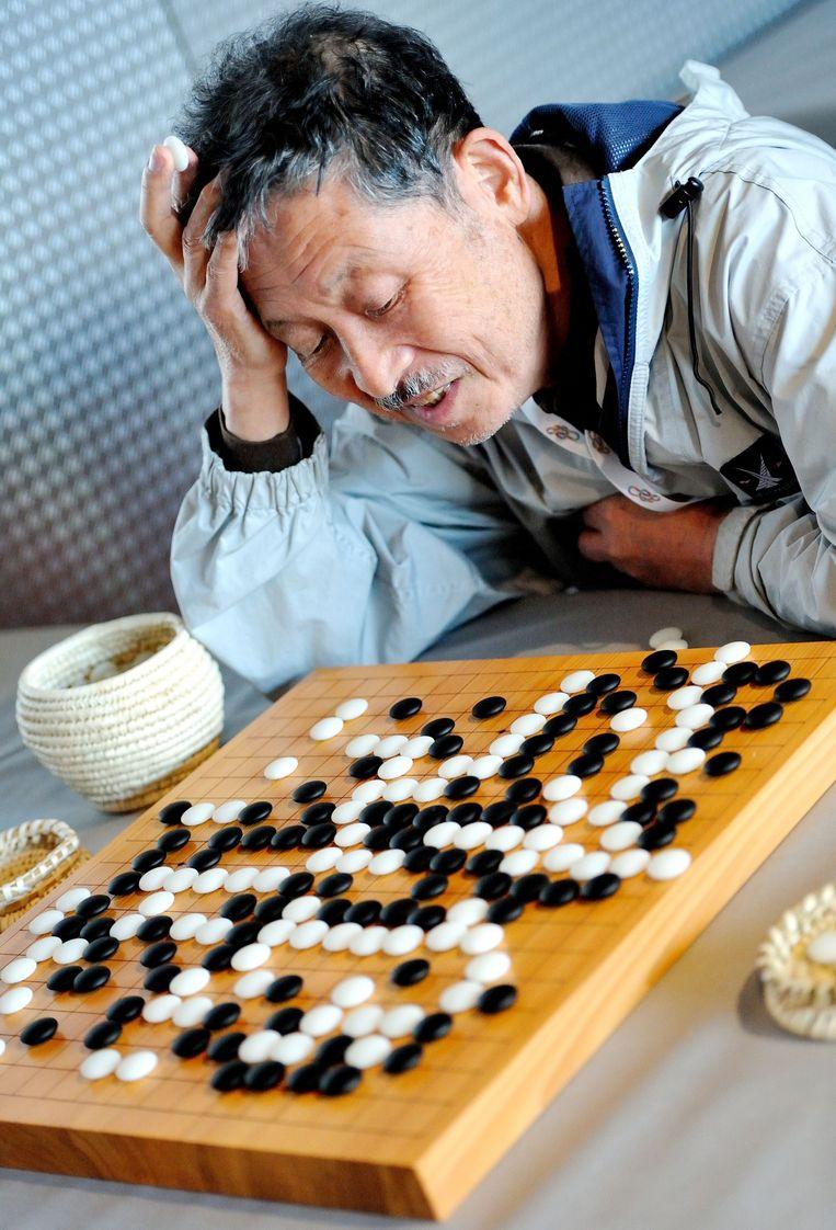 Een man breekt zich het hoofd over een spelletje Go. Beeld AFP