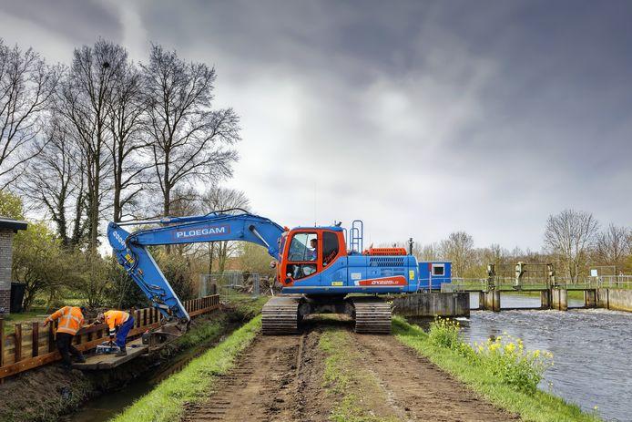 Werk aan de nieuwe beschoeiing bij de Essche Stroom. Waterschap De Dommel gaat hier de waterkering verhogen met bijna een meter.