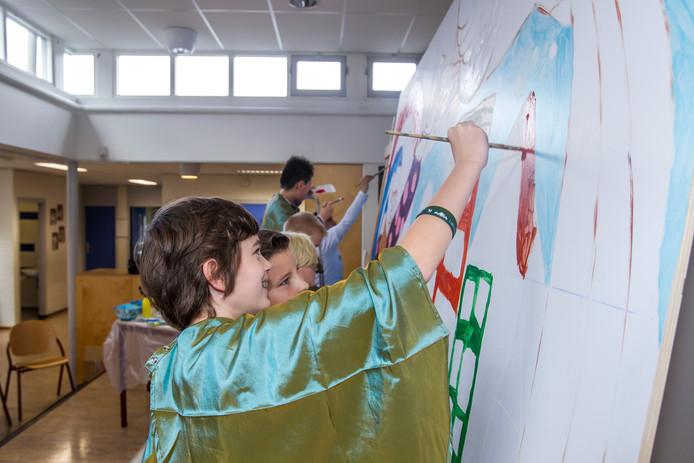 Kinderen van de Montessorischool in Helmond druk aan het schilderen.