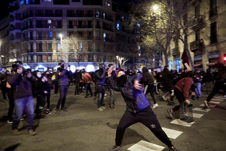 Betogers gooien in Barcelona onder meer met stenen naar de politie tijdens een protestmars tegen de arrestatie van de rapper Pablo Hasél. Beeld EPA