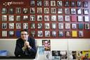Docent Nederlands Jos Lanters poseert trots voor de wand met tientallen foto's van schrijvers die hij naar het OLV heeft gehaald. foto Joyce van Bellekom/het fotoburo