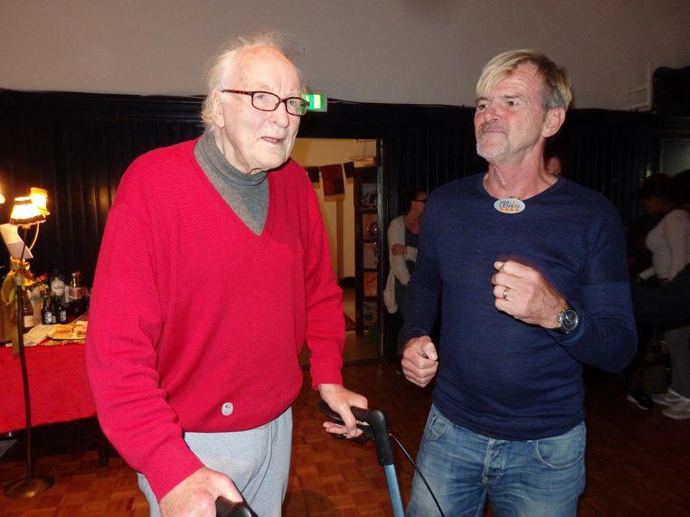Arie van den Boogaart, vrolijk schuifelend achter zijn rollator, met vrijwilliger Karel (Vier het leven). Beeld Schuim