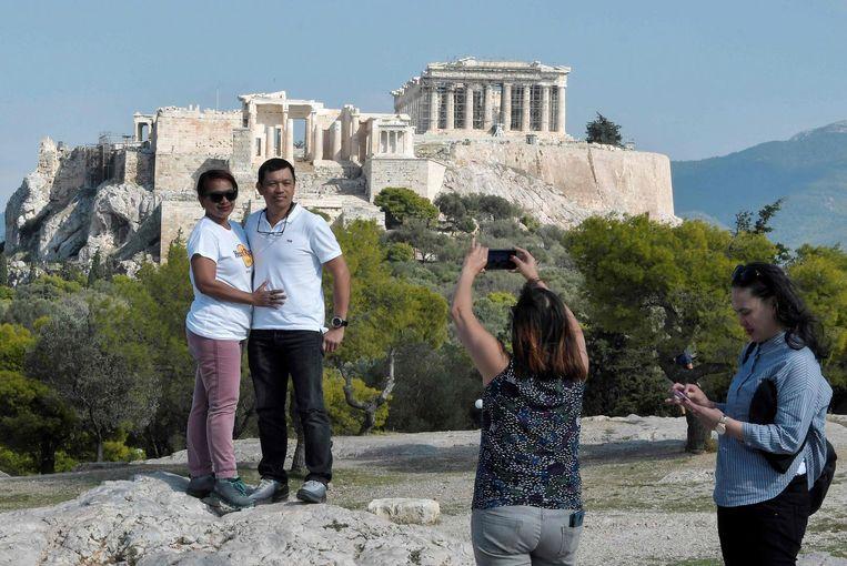 Een koppel poseert voor de Akropolis in Athene. Beeld afp