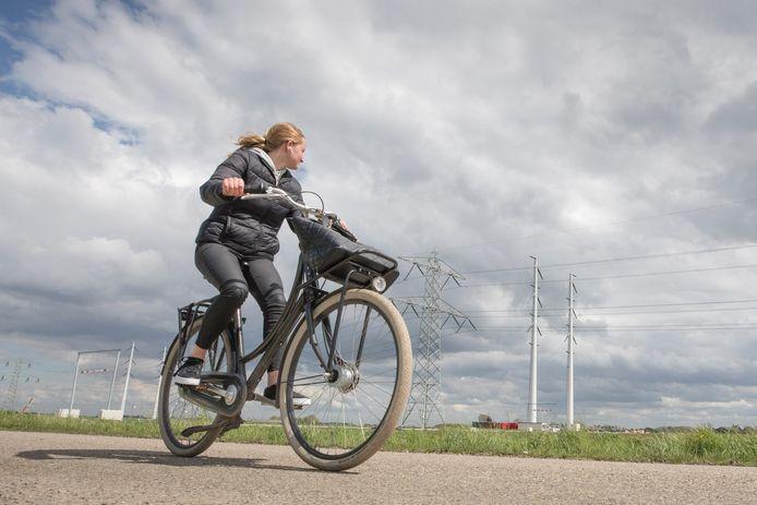 Een fietsster op de Bimmelsweg werpt een blik op de nieuwe masten. Vanwege de plaatsing daarvan was de doorgaande fietstroute via De Poel naar Goes maandenlang dicht.
