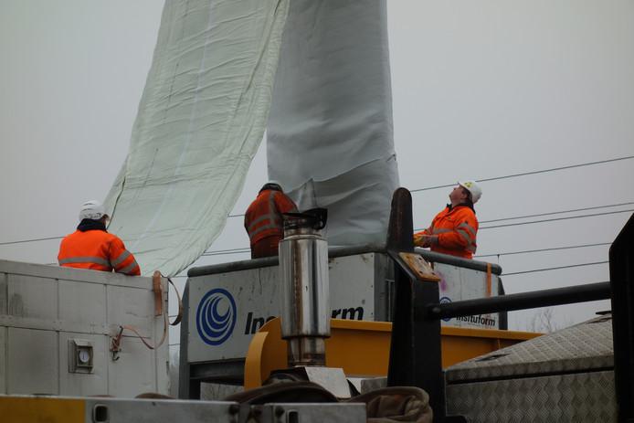 Met behulp van een kraan wordt een lange polyester kous in het riool gehesen.