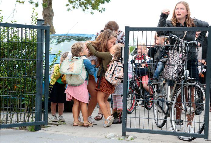 Een afscheidskus aan de poort, voor het begin van de eerste schooldag op de Noahschool in Schoonrewoerd.