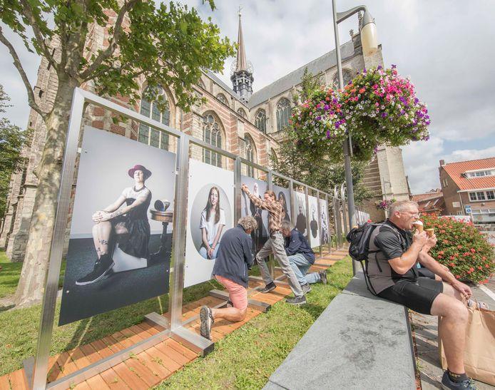 Terwijl toeristen rustig een ijsje weglikken zijn Peter van de Korput, Caspar Mulders en Wim Bakker (vlnr) druk bezig om de panelen van de tentoonstelling 'Goese Meisjes, Pront en Bont' op te hangen.