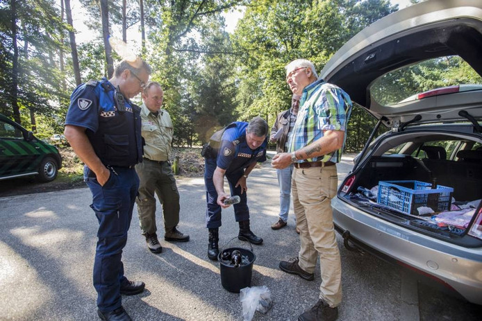 Jan van Hulst laat handhavingsambtenaren van de gemeente zien wat hij aan glas en asbestmateriaal zoal bij elkaar sprokkelt op de bospaden.