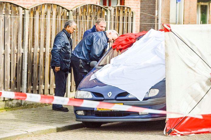 Agenten onderzoeken de auto waarin een dode man is aangetroffen.