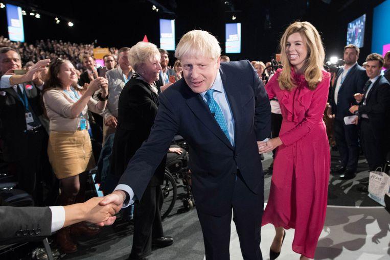 De Britse premier Boris Johnson met zijn partner Carrie Symonds op het partijcongres van de Conservatieve Partij.   Beeld EPA