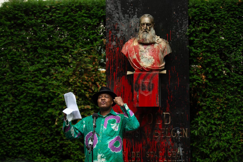 Een activist geeft een speech bij een bekladde buste van Leopold II. Beeld BELGA