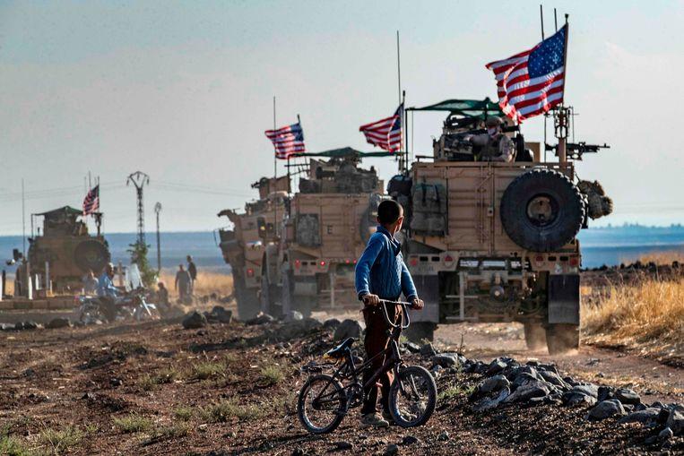 Een Syrische jongen bij een konvooi van Amerikaanse voertuigen in Noord-Irak, bij de grens met Turkije, eind 2019.   Beeld AFP