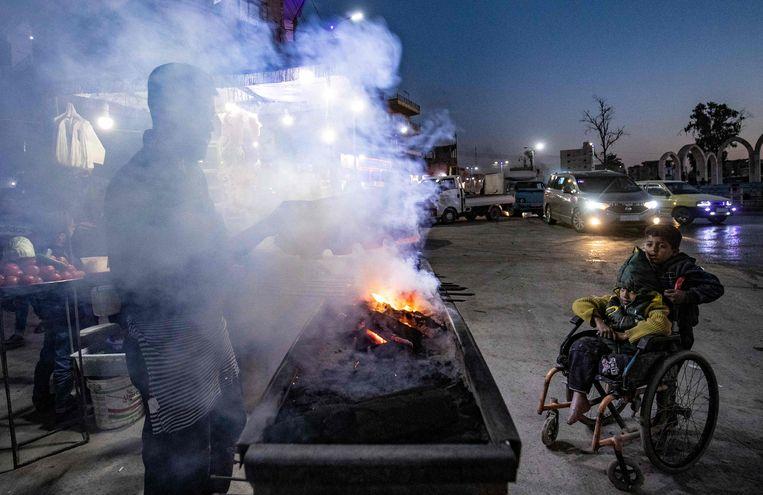 Een man grillt eten op een houtskoolbarbecue in Raqqa. Beeld AFP