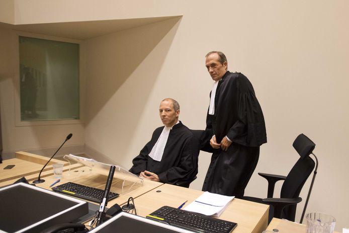 De twee officieren van Justitie Mol en Sleeswijk tijdens de rechtszaak.  Achter het raam zitten de twee verdachte agenten DH01 en DH02. Foto Olaf Kraak