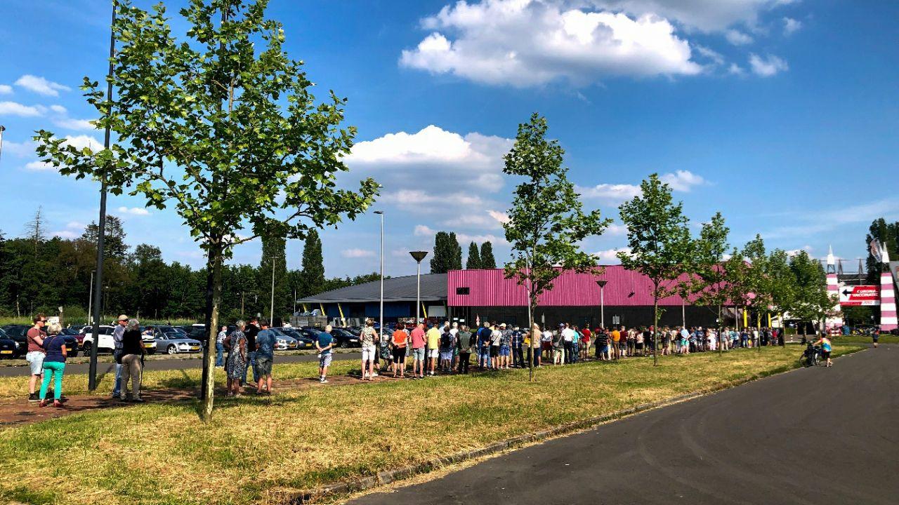 Een enorme rij met mensen die een stempel in hun gele boekje willen laten zetten in Enschede.