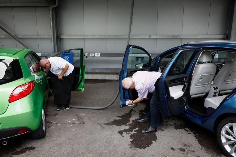 Meneer Lenz (rechts) poetst zijn Mercedes. 'Als de Duitse autobranche instort, zal de crisis ook elders in Europa voelbaar zijn.' Beeld Daniel Rosenthal / de Volkskrant