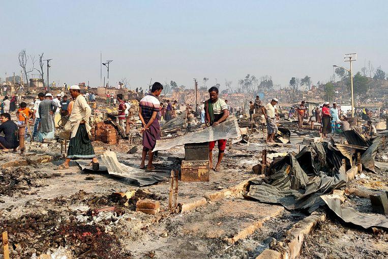 Rohingya-vluchtelingen doorzoeken het puin op de plek waar hun onderkomen is afgebrand na een brand die uitbrak in een Rohingya-vluchtelingenkamp in Cox's Bazar in Bangladesh. Beeld Reuters