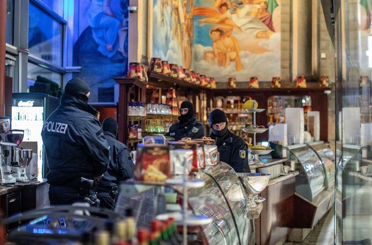 ► Duitse politieagenten voeren een raid uit op een café in Duisburg, West-Duitsland. De actie was gericht tegen de 'Ndrangheta, waarvan 90 leden zijn opgepakt. Beeld Christoph Reichwein/dpa
