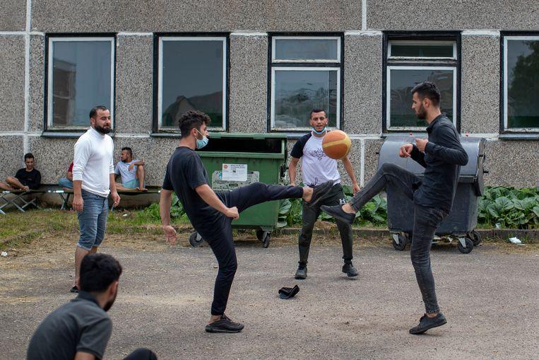 Migranten uit Irak spelen met een bal in een vluchtelingenkamp in het dorp Verebiejai, 145 kilometer ten zuiden van Vilnius.  Beeld AP