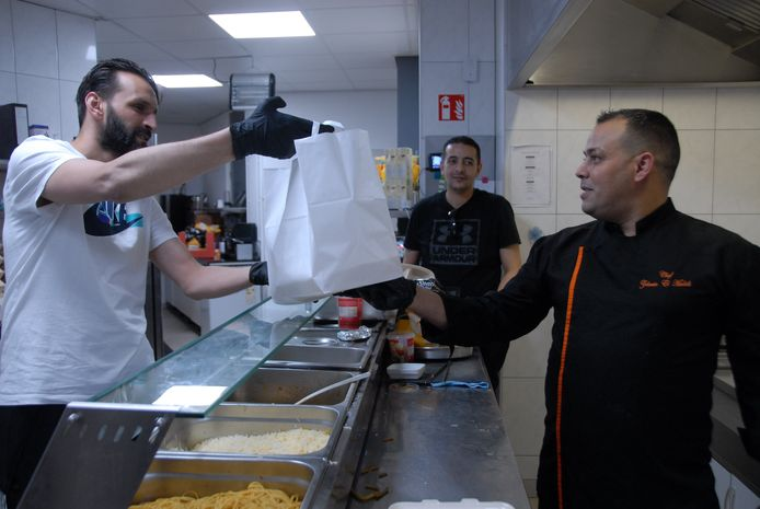 Badr Battaioui(l) krijgt van chef-kok Zakaria el Madidi een papieren tas met daarin een iftarmaaltijd aangereikt.