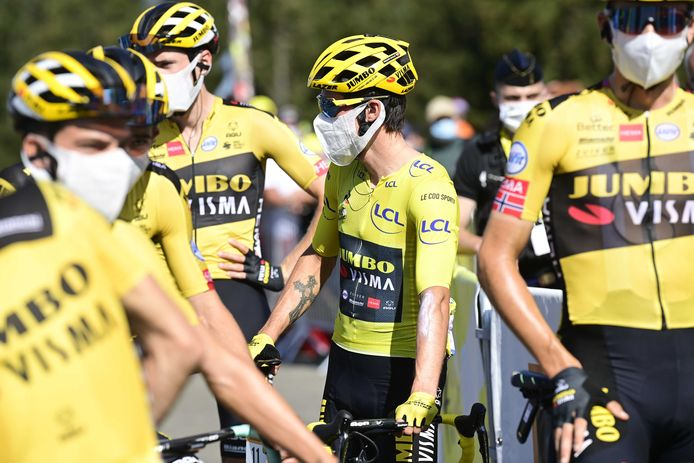 De renners van Jumbo-Visma, met Roglic in de gele trui, met een mondkapje voor hun gezicht.
