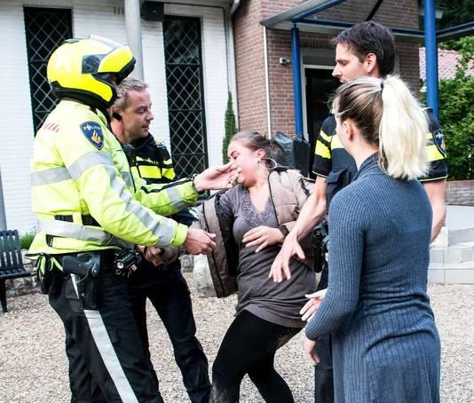 Agenten arresteren een vrouw die demonstreert tegen het houden van een dansvoorstelling op de Algemene Begraafplaats Westerweg.
