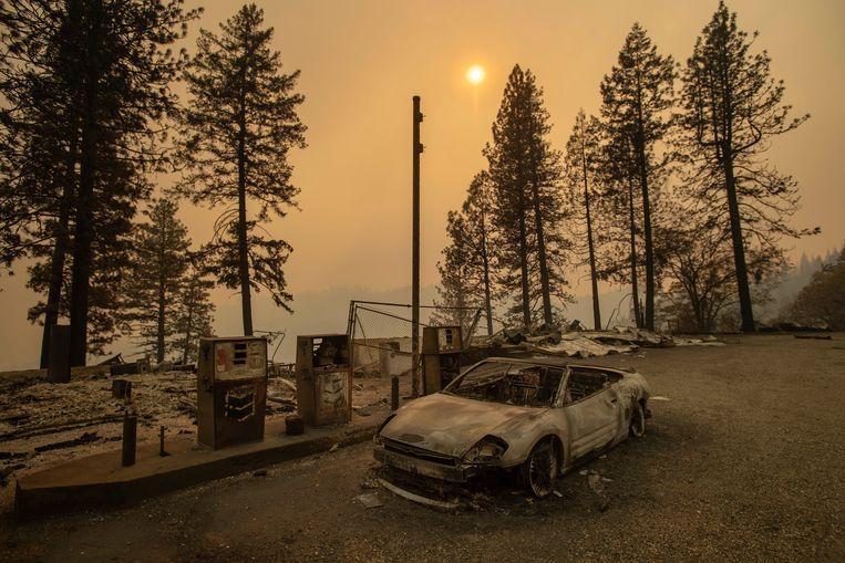 Een verbrande auto bij een verwoest benzinestation in Pulga, Californië.  Beeld AP