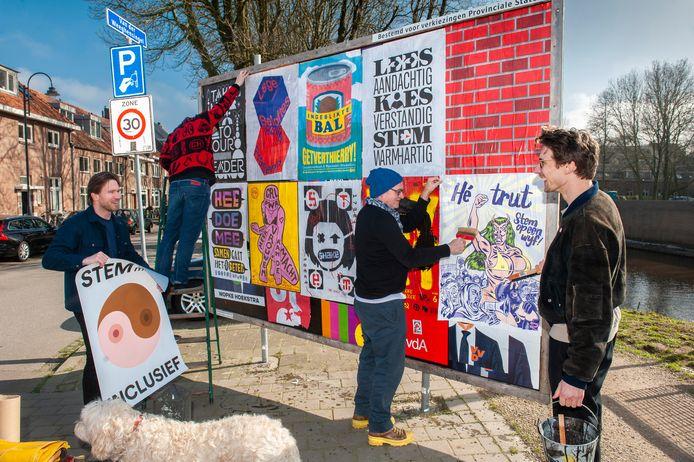 Edwin Vollebergh van Studio Boot (2e rechts) plakt samen met de initiatiefnemers van de politiek-affiche-ontwerpwedstrijd de eigentijdse affiches op een verkiezingsbord aan de Van der Weeghensingel in Den Bosch.