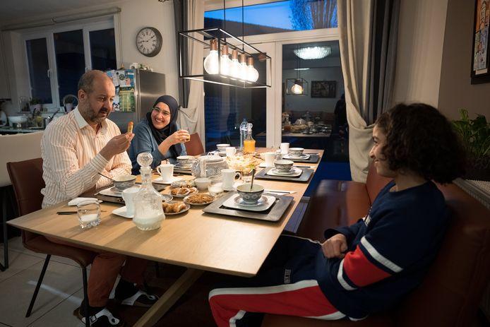 Rafik Faiz (53), Zinab El Jaouhare (45) en hun zoontje Reda (16) aan tafel tijdens de iftar.
