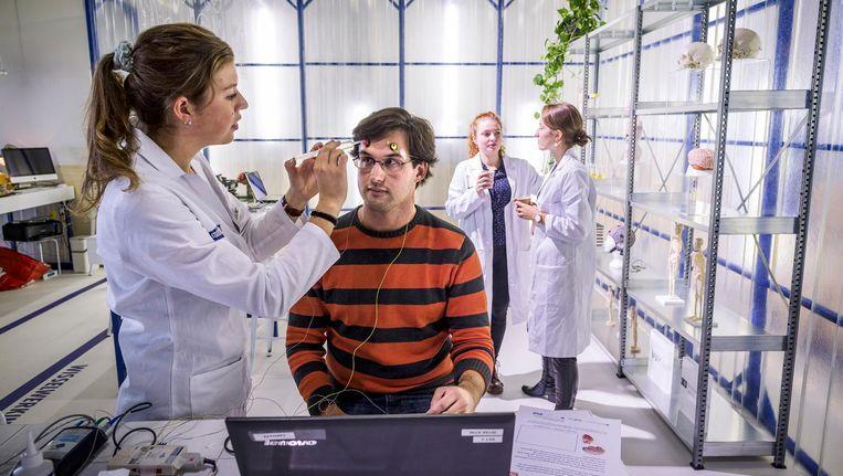 Een student meet in het laboratorium op CS de hersenactiviteit van een reiziger Beeld Rink Hof