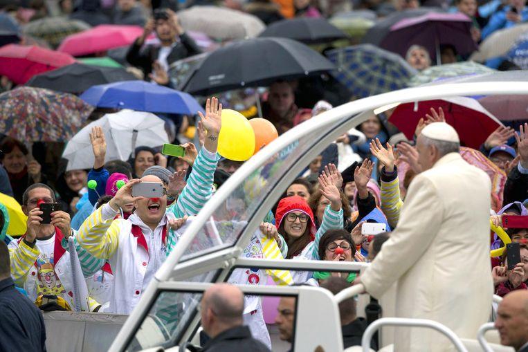 De paus wordt toegezwaaid door een aantal clowns als hij arriveert voor zijn wekelijkse audiëntie op het Sint-Pietersplein, Vaticaanstad, december 2014. Beeld ap