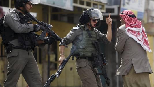 Een politieagent van de Israëlische grens schreeuwt naar een oude man tijdens rellen in Hebron.